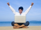 Picture of a businessman sitting on the beach with a laptop in his lap and arms in the air